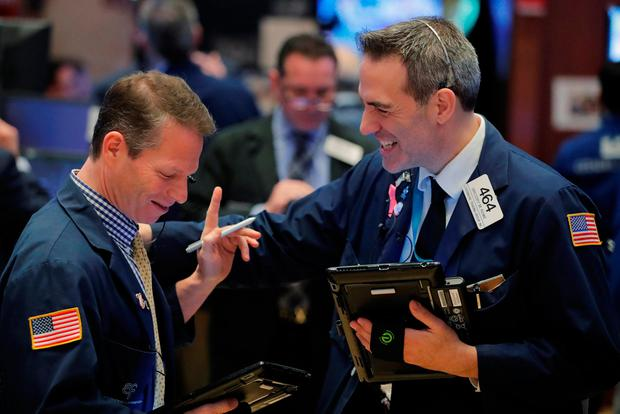 Traders laugh as they work on the floor of the New York Stock Exchange shortly after the opening bell in New York