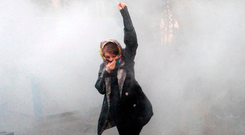 An Iranian woman raises her fist amid the smoke of tear gas at the University of Tehran during a protest driven by anger over economic problems, in the capital Tehran. Photo: STR/AFP/Getty Images