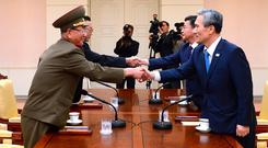 South Korean National Security Director, Kim Kwan-jin, right, and Unification Minister Hong Yong-pyo, second from right, shake hands with Hwang Pyong So, left, North Korea' top political officer for the Korean People's Army, and Kim Yang Gon, a senior North Korean official responsible for South Korean affairs, during their meeting at the border village of Panmunjom in Paju, South Korea. Photo: PA