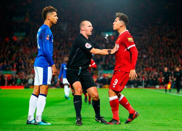 Referee Robert Madley intervenes as Mason Holgate of Everton and Roberto Firmino of Liverpool Photo: Clive Brunskill/Getty Images