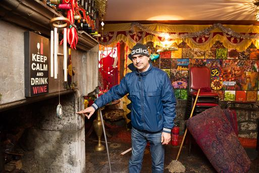 Ram Kumar shows the level of the water that rushed into his restaurant Kumar's Taste of Asia as customers were ordering from him in Galway City. Photo: Andrew Downes, XPOSURE