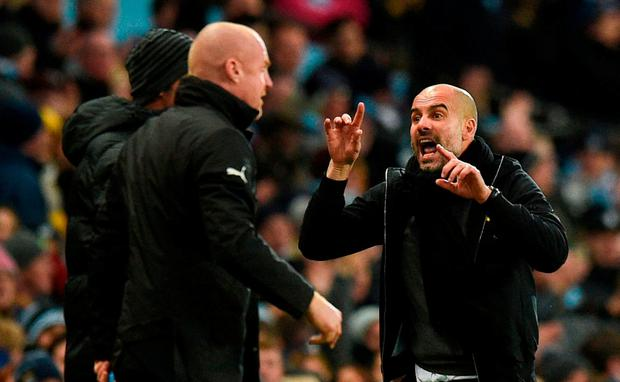 Manchester City's Spanish manager Pep Guardiola (R) gestures to Burnley's English manager Sean Dyche (L) during the English FA Cup third round football match between Manchester City and Burnley at the Etihad Stadium