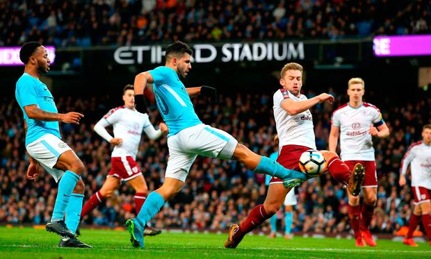 Sergio Aguero of Manchester City crosses the ball under pressure from Charlie Taylor of Burnley