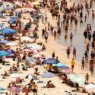 Beachgoers sit and walk in the water at Sydney's Bondi Beach on a hot summer day in Australia, January 7, 2018. AAP/Glenn Campbell/via REUTERS