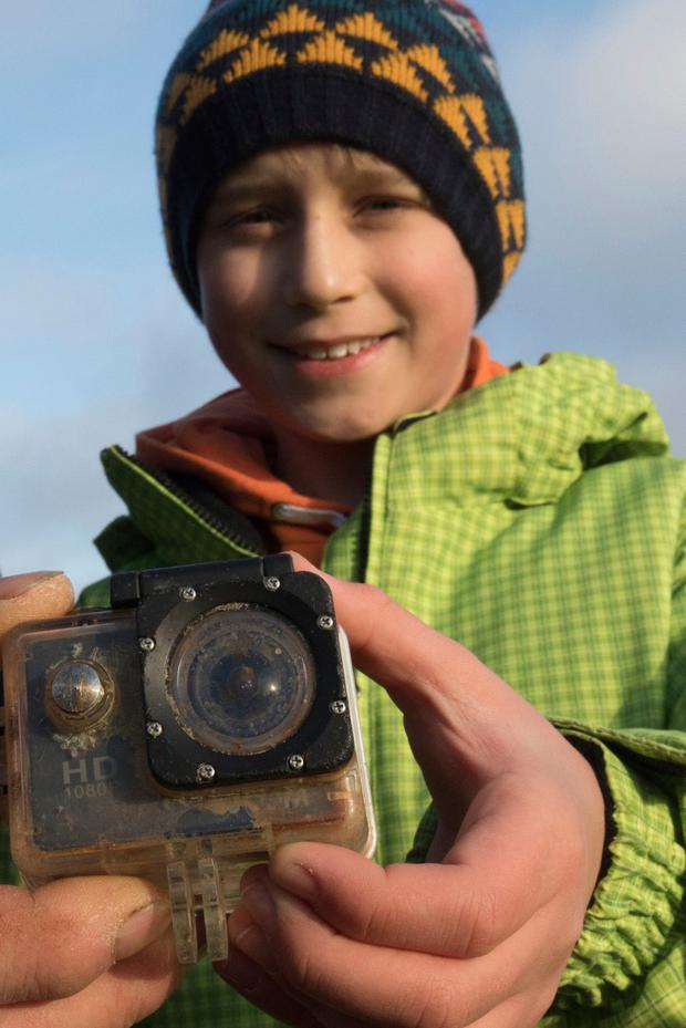 Britain's William Etherton holds a camera on the North Sea island of Suederoog, Germany, Saturday, Jan. 6, 2018. The English boy has been reunited in Germany with a video camera he lost four months ago on the other side of the North Sea. News agency dpa reported that the camera was handed back to the 10-year-old Saturday on Suederoog, a small island off GermanyÕs western coast a little south of the Danish border. (Christian Charisius/dpa via AP)