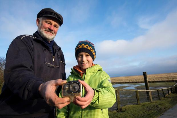 William Etherton and Roland Spreer hold a camera on the North Sea island of Suederoog, Germany