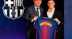 Barcelona's new Brazilian midfielder Philippe Coutinho poses with his new jersey beside Barcelona FC President Josep Maria Bartomeu