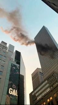 A smoke is seen rising from the roof of Trump Tower, in New York, U.S., January 8, 2018 in this still image obtained from social media video. TWITTER/@NYCBMD/via REUTERS
