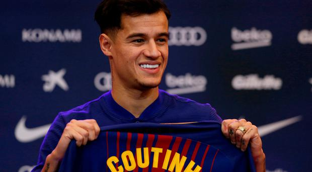 Barcelona's new signing Brazilian Philippe Coutinho poses for the media, during his official presentation at the Camp Nou