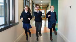Allie Ní Threasaigh, Eoin Seoighe and Grace Cheung run through the hallways of Gaelscoil Mhic Amhlaigh. Photos: Andrew Downes