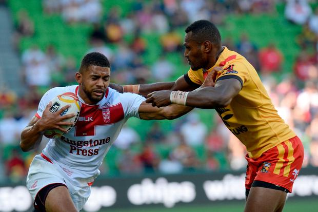 Kallum Watkins (L) is tackled by Kato Ottio of Papua New Guinea