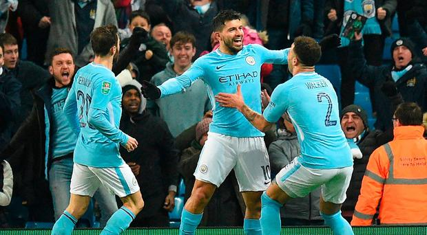 Manchester City's Argentinian striker Sergio Aguero (C) celebrates with teammates after scoring their late winning goal during the English League Cup semi-final first leg football match between Manchester City and Bristol City at the Etihad