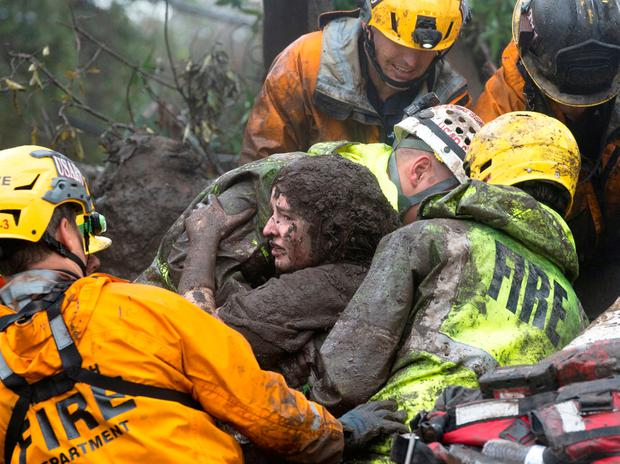 Emergency personnel carry a woman rescued from a collapsed house after a mudslide in Montecito, California, U.S. January 9, 2018. Kenneth Song/Santa Barbara News-Press via REUTERS