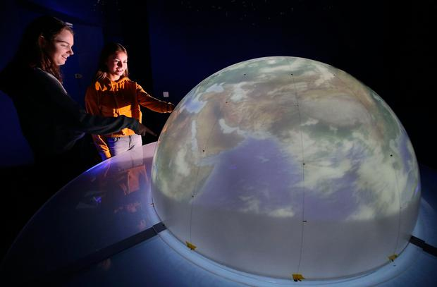 Transition year students Eleanor Grennan (15) and Eva Whelan (15) from Loreto Abbey in Dalkey view a model of the earth at the Cool Planet Experience. Photo: Damien Eagers