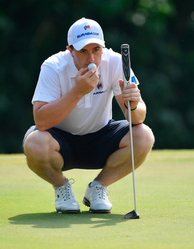 Paul Dunne mulls over a putt during a practice round yesterday ahead of the EurAsia Cup in Kuala Lumpur. Photo: Stuarty Franklin/Getty Images