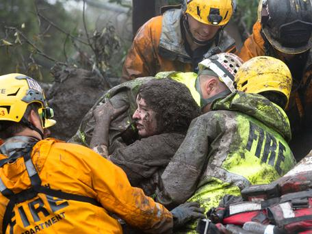 Rescuers carry a woman pulled from a collapsed house. Photo: Reuters