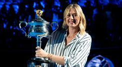 Former ladies single's champion Russia's Maria Sharapova poses for a photo with the Daphne Akhurst Memorial Cup on Margaret Court Arena during the ceremony for the official draw at the Australian Open tennis championships in Melbourne