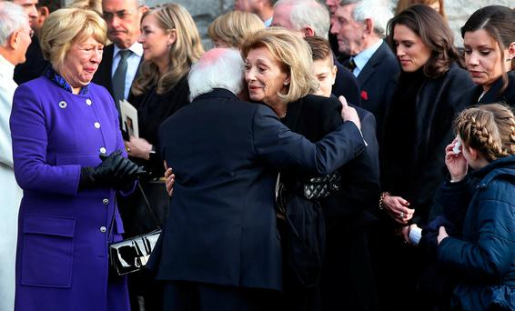President Michael D Higgins and wife Sabina comfort the late Peter Sutherland's wife Maruja at the Church of the Sacred Heart in Donnybrook after his funeral Mass yesterday. Photo: Steve Humphreys