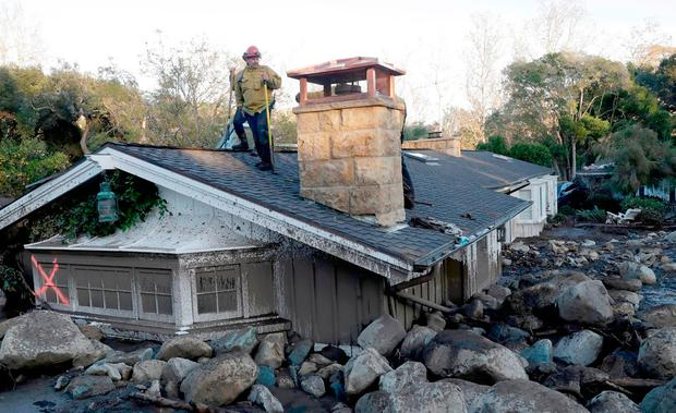 Afirefighter stands on the roof of a house submerged by mud and rocks in Montecito. Photos: Marcio Jose Sanchez/AP
