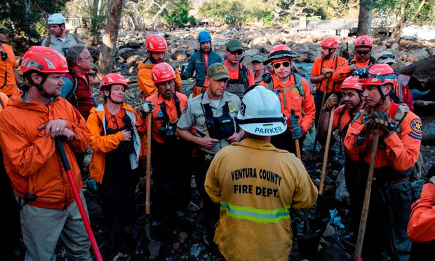 Left, search and rescue volunteers are updated by a Ventura County firefighter as they prepare to search for missing victims