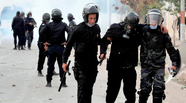 A wounded riot police officer is evacuated during anti-government protests, in Tebourba, south of the Tunisian capital, Tunis. Photo: AP