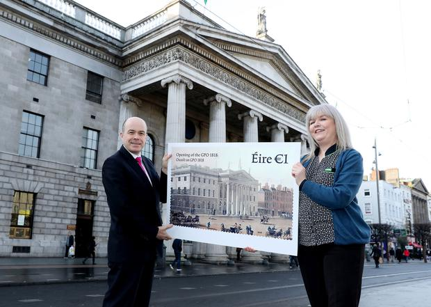 Minister Denis Naughten and GPO clerk Debbie Gilligan unveil the new stamp. Photo: Maxwells Dublin