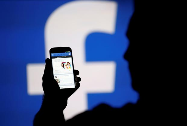 A man is silhouetted against a video screen with an Facebook logo as he poses with an Samsung S4 smartphone in this photo illustration REUTERS/Dado Ruvic/File Photo