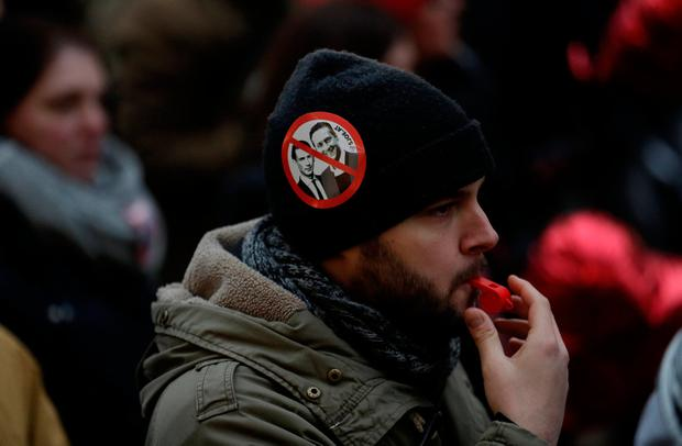 A protestor blows a whistle during an anti-government demonstration in Vienna, Austria January 13, 2018. REUTERS/Heinz-Peter Bader