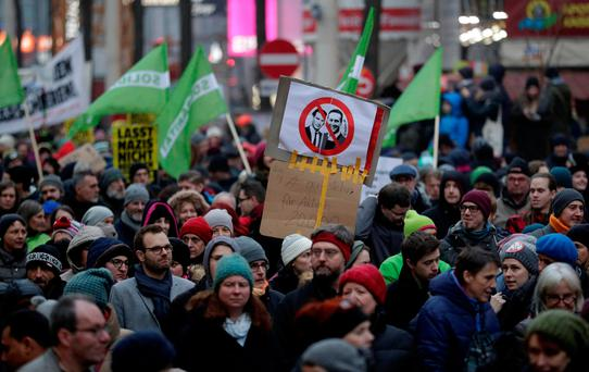 Protesters hold a sign with portraits of Austrian Chancellor Sebastian Kurz and Vice Chancellor Heinz-Christian Strache during an anti-government demonstration in Vienna, Austria January 13, 2018. REUTERS/Heinz-Peter Bader