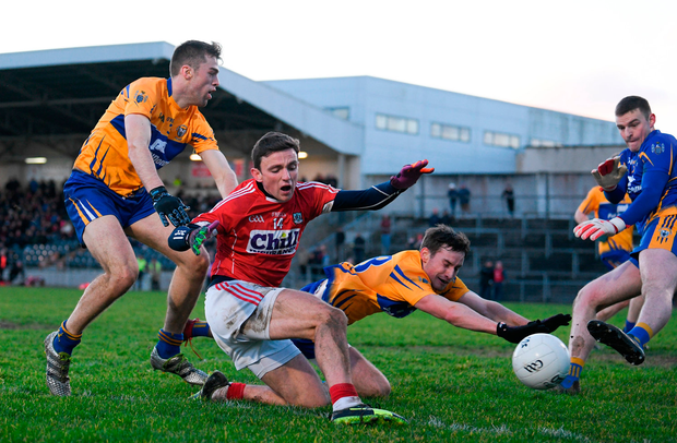 Mark Collins of Cork in action against Cillian Brennan, Eoghan Collins, and Clare goalkeeper Killian Roche during the McGrath Cup Final. Photo: Diarmuid Greene/Sportsfile