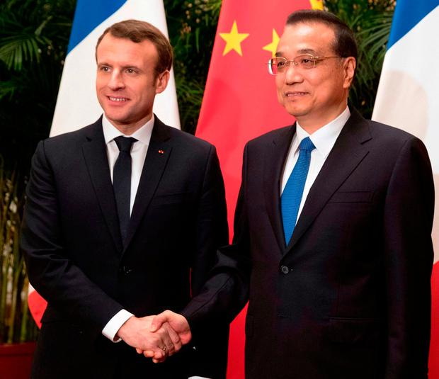 HOPE: French President Emmanuel Macron, left, meets Chinese Premier Li Keqiang in Beijing for discussions on climate change. Photo: Mark Schiefelbein/AP