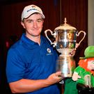 Paul Dunne celebrates with the trophy after Europe's victory. Photo: Getty Images