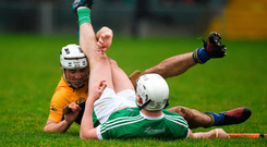 Clare's Patrick O'Connor and Aaron Gillane of Limerick end up in a tangle on the Gaelic Grounds pitch during the Superstores Munster SHL Final. Photo: Diarmuid Greene/Sportsfile