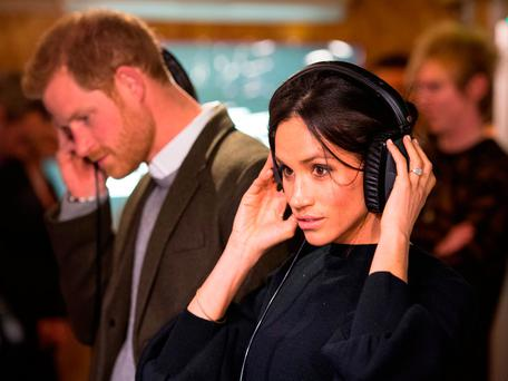 Prince Harry and Meghan Markle listen to a broadcast through headphones during a visit to radio station Reprezent FM in London Photo: Dominic Lipinski/PA Wire