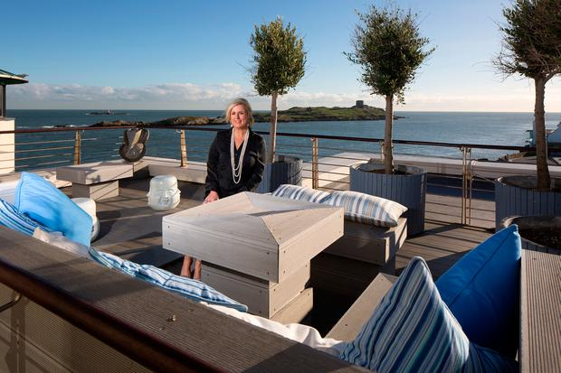 Jewellery designer Helen Gallagher on the magnificent deck of her penthouse apartment, which has views stretching from Dalkey Island to Howth. The deck furniture, designed by Corinna Knaggs, had to be built in, otherwise it would have blown off in extreme conditions, such as during Storm Ophelia. Photo: Tony Gavin