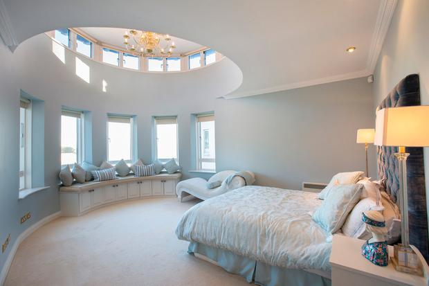 The master bedroom in Helen Gallagher's duplex apartment with its stunning views, and cupola-style ceiling, is decorated in shades of blue and sand to echo the coastal location. Photo: Tony Gavin
