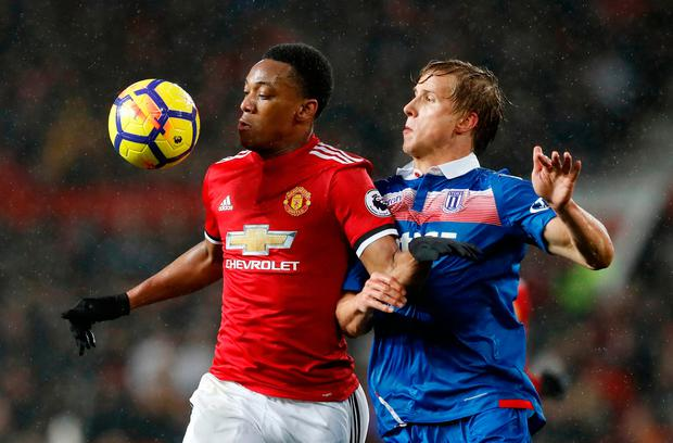Manchester United's Anthony Martial and Stoke City's Moritz Bauer (right) battle for control of the ball Photo: Martin Rickett/PA Wire