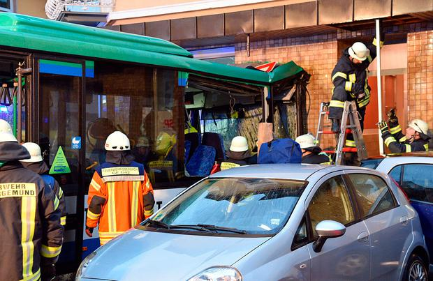Firefighters work beside a bus sitting in the facade of a building in Eberbach near Mannheim, southern Germany, Tuesday, Jan 16, 2018. Several students inside the school bus have been injured. (Rene Priebe/dpa via AP)