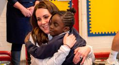 Catherine, Duchess of Cambridge, Patron of the All England Lawn Tennis and Croquet Club (AELTC) receives a hug during a visit to Bond Primary School in Mitcham to see the work of the Wimbledon Junior Tennis Initiative (WJTI) on January 17, 2018 London, United Kingdom. (Photo by Arthur Edwards - WPA Pool/Getty Images)