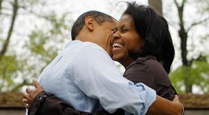 Barack Obama hugs his wife Michelle while meeting families during a picnic at a park in Noblesville, Indiana, May 03, 2008. AFP PHOTO/Emmanuel Dunand / AFP / EMMANUEL DUNAND