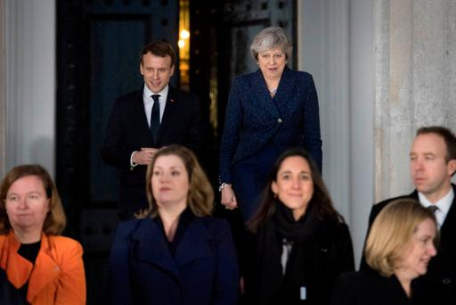 Britain's Prime Minister Theresa May and France's President Emmanuel Macron walk to pose for a family photo at the Royal Military Academy Sandhurst, during UK-France summit talks in Sandhurst, Britain, January 18, 2018. REUTERS/Stefan Rousseau/Pool