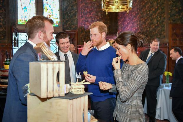Britain's Prince Harry and his fiancée US actress Meghan Markle taste traditional Welsh cakes during a visit at Cardiff Castle in Cardiff, south Wales on January 18, 2018, for a day showcasing the rich culture and heritage of Wales. / AFP PHOTO / POOL / Ben Birchall (Photo credit should read BEN BIRCHALL/AFP/Getty Images)