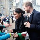 CARDIFF, WALES - JANUARY 18: Meghan Markle writes a note for 10 year old Caitlin Clarke from Marlborough Primary School as Prince Harry looks on during a walkabout at Cardiff Castle on January 18, 2018 in Cardiff, Wales. (Photo by Chris Jackson/Getty Images)
