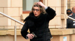 A gunman, dressed as a woman and wearing a wig, pictured with a gun outside the hotel