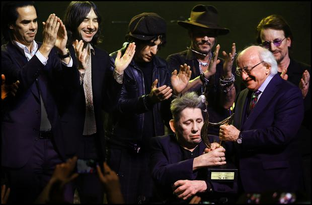 Shane is presented with a lifetime achievement award by President Michael D Higgins, flanked by Nick Cave, Bobby Gillespie, Carl Barrat, Johnny Depp and Bono
