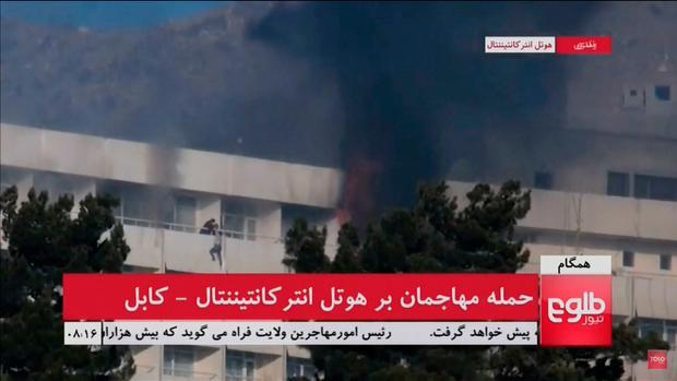 A man is seen dangling off a balcony of Kabul's Intercontinental Hotel, after gunmen attacked the hotel, in Kabul, Afghanistan, in this still image taken from a video supplied by TOLOnews January 21, 2018. TOLOnews/Reuters TV/via REUTERS