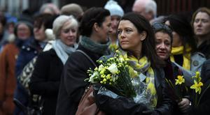 Schoolfriends bring yellow flowers to represent sunshine as they queue up to view Cranberries singer Dolores O'Riordan's coffin as it is carried into St. Joseph's Church for a public reposal in Limerick, Ireland January 21, 2017. REUTERS/Clodagh Kilcoyne