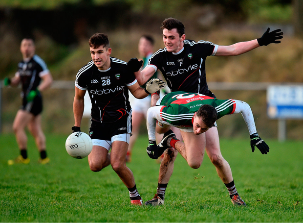 Diarmuid O'Connor of Mayo goes flying through the air as he battles for the ball with Sligo pair Vincent Frizell (left) and Finnian Cawley. Photo by Seb Daly/Sportsfile