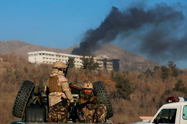 Afghan security forces stand guard as smoke rises behind them from the charred remains of the Intercontinental Hotel in Kabul. Photo: REUTERS/Omar Sobhani