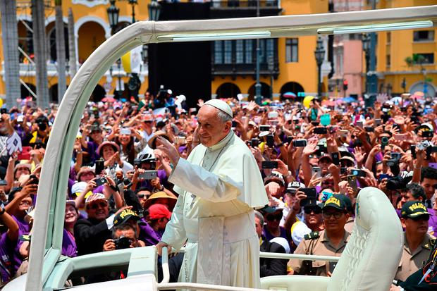 Pope Francis waves from the popemobile to the crowd of faithfuls gathered at Plaza de Armas square in Lima, after delivering his Angelus prayer. Photo: AFP/Getty Images